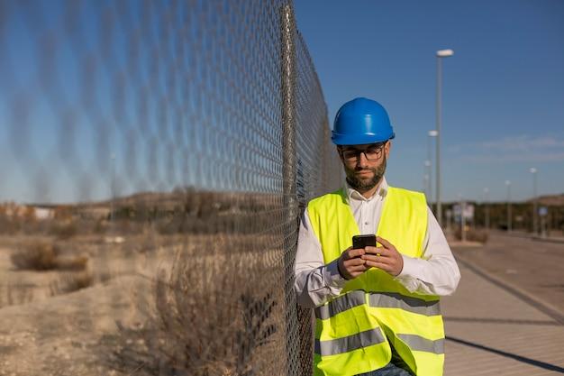 Архитектор или инженер с помощью мобильного телефона на строительной площадке.