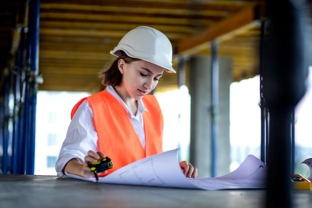 건축가 또는 엔지니어가 작업하고, 청사진 계획이 있는 건설 현장 내부의 건물 프로젝트를 탐색합니다. 여성 건설 엔지니어 또는 건축가 일하는 사람들.