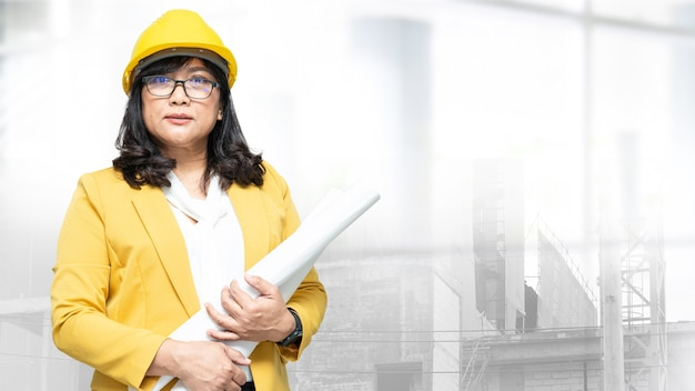 建築家またはエンジニアは、建築現場でプロジェクトの会計および建設用ヘルメットを作業します