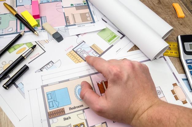 Архитектор рассматривает и показывает план. архитектурный эскиз.