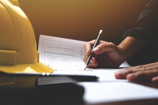 건축가 데스크 : 엔지니어는 사무실에서 도면을 사용합니다. 디자이너를위한 기기 및 사무실. 근접 남성 손에 연필로 그립니다.