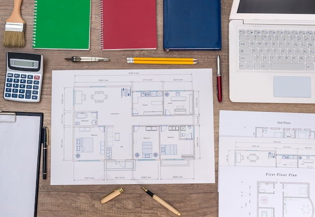 Architect's work place with house plan, laptop and calculator