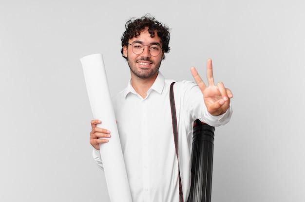 建築家は笑顔で幸せそうに見え、のんきで前向きで、片手で勝利または平和を身振りで示します