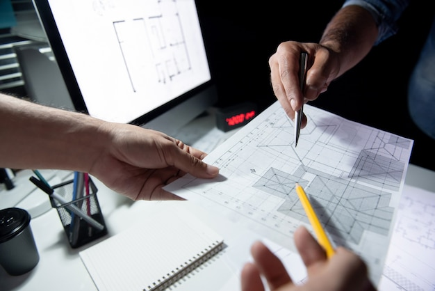 Architect team discussing blueprint paper in office at night