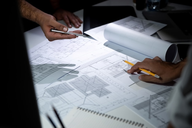 Architect team discussing blueprint paper in office