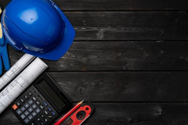 건축가 도구는 안전모, 청사진 및 계산기 평면도로 부각됩니다.