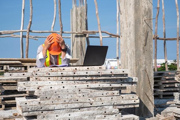 Архитектор, используя ноутбук на строительной площадке