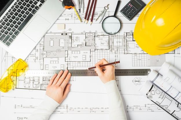 Architect using ruler on blueprint