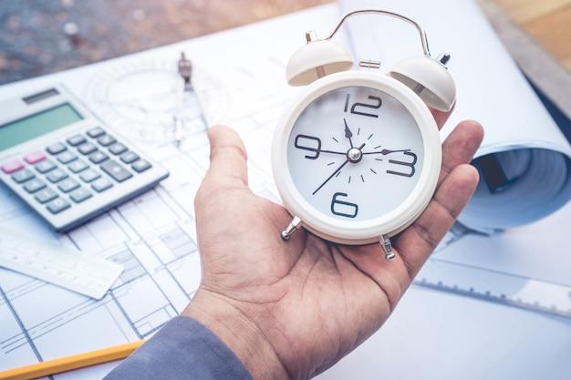 計画設計紙に目覚まし時計を持つ建築家