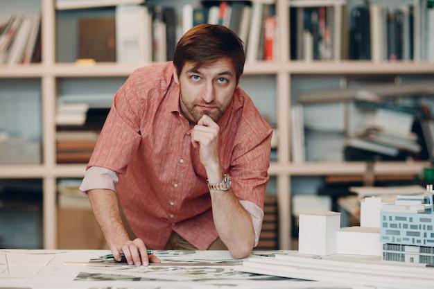 Архитектор с чертежами и дизайн-проектом макета в бюро архитектуры