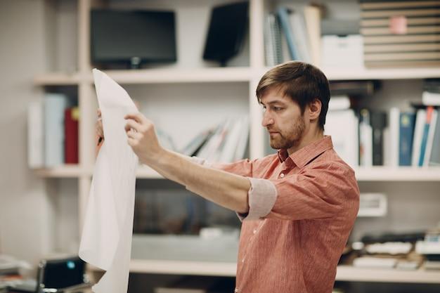Архитектор с чертежами и дизайн-проектом макета в офисном бюро