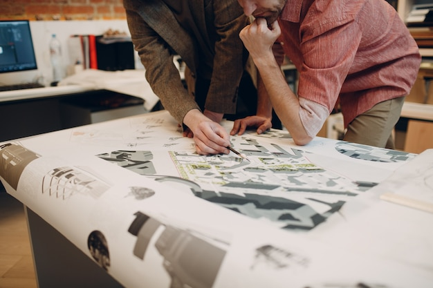事務所局で設計図とレイアウト設計プロジェクトを持つ建築家