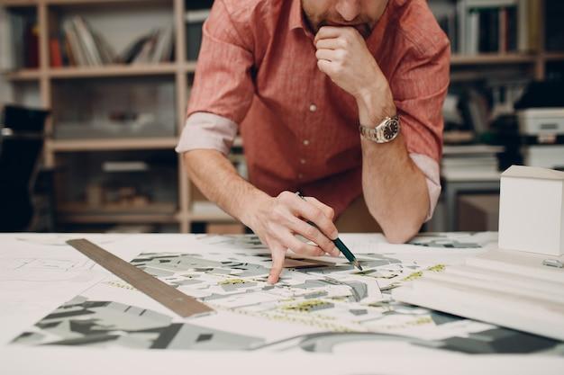 設計図とオフィスでのレイアウト設計プロジェクトを持つ建築家