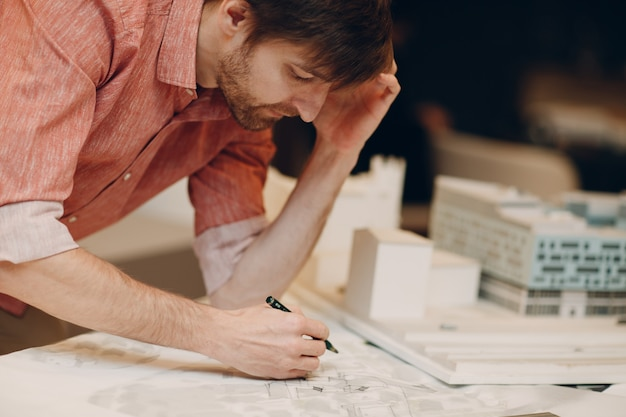 Architect with blueprints and layout design project at architectural bureau