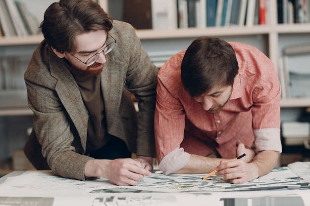 Architect with blueprints and layout design project at office bureau
