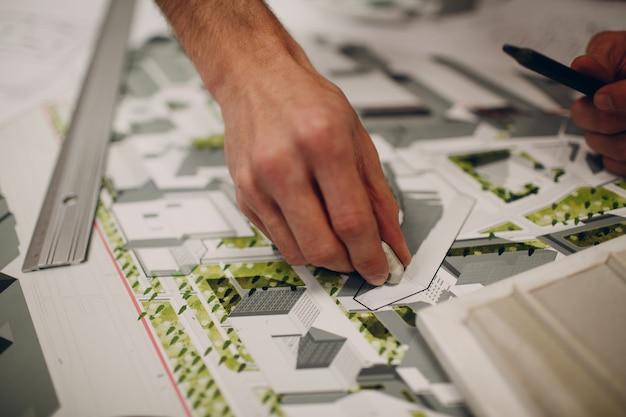Архитектор с ластиком резиновые чертежи и дизайн-проект макета в офисном бюро