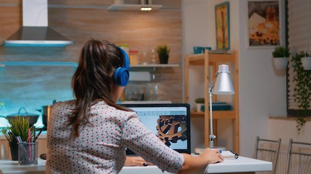 밤에 부엌에 앉아 집에서 일하는 동안 노트북을 사용하여 무선 헤드셋을 사용하는 건축가. cad 소프트웨어를 보여주는 개인용 컴퓨터에서 공부하는 산업 여성 엔지니어.