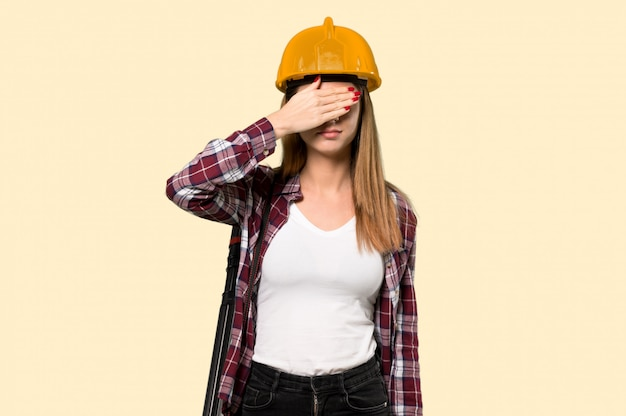 Architect woman covering eyes by hands. do not want to see something  on yellow
