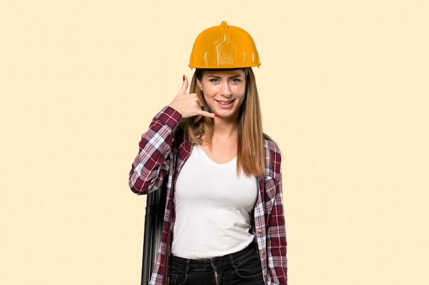 Architect woman making phone gesture. call me back sign  on yellow