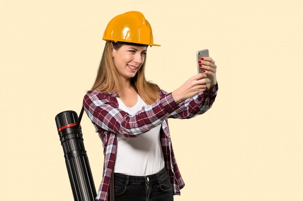 Architect woman making a selfie over isolated yellow