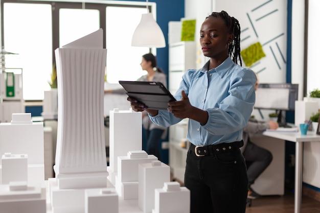 プロのマケットの建物のモデルを見てタブレットに取り組んでいるアフリカ系アメリカ人の建築家の女性。開発中の現代プロジェクトの設計を表示する建築労働者