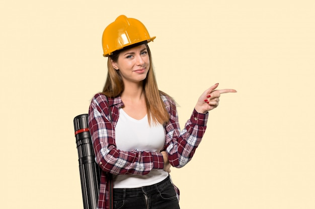 Architect woman pointing finger to the side over isolated yellow wall