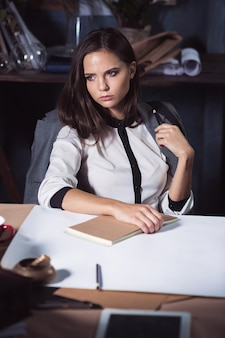 Architect woman working on drawing table in office or home.