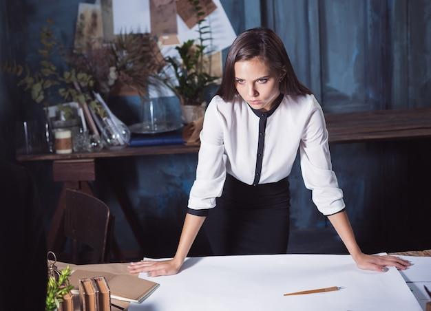 オフィスや家で図面のテーブルに取り組んでいる建築家の女性。スタジオ撮影