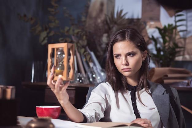 Женщина архитектора, работающая над чертежным столом в офисе или дома с песочными часами. понятие нехватки времени