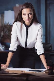 Женщина-архитектор, работающая над чертежным столом в офисе или дома
