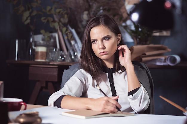 オフィスでテーブルを描くことに取り組んでいる建築家の女性