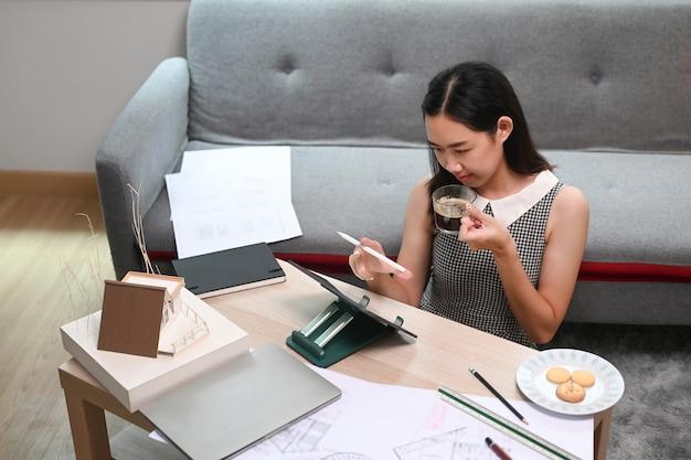居間でコンピューターのタブレットと青写真を扱う建築家の女性。