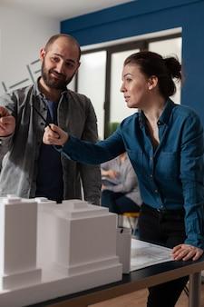 マケットの建物のモデルと机に立って専門のオフィスで話している建築家の作業チーム。建設レイアウトの青写真を設計しようとしている白人のプロジェクトパートナー