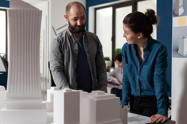 専門のオフィスで話している建築家の作業チーム