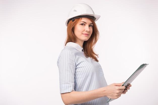 Концепция архитектора, рабочего и риэлтора - женщина-строитель или инженер в шлеме с документами на белом