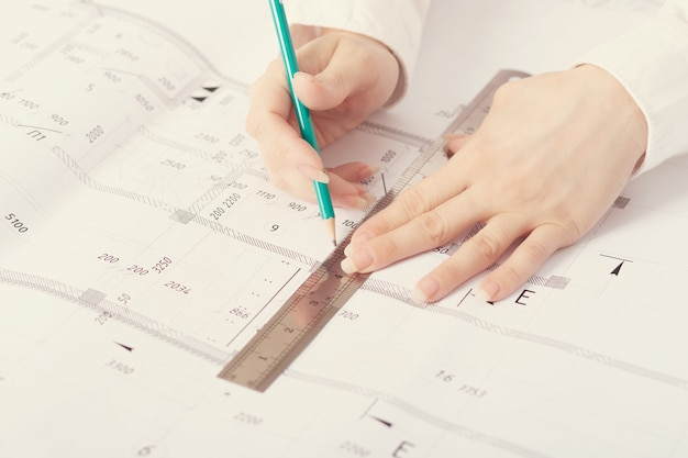 Architect working on blueprint, with architectural project at construction site at office desk in office