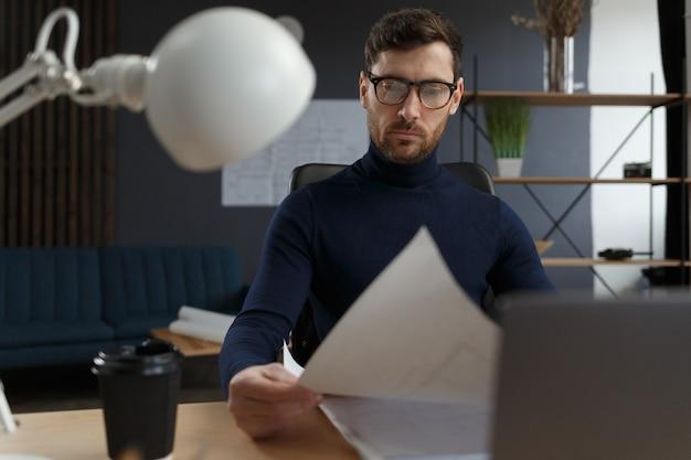 Архитектор, работающий в офисе с проектировщиком, проверяет архитектурный план, создавая эскиз конструкции ...