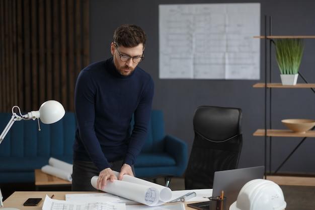 ブループリントエンジニアと一緒にオフィスで働く建築家は、構造をスケッチする建築計画を検査します...