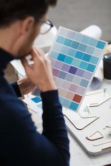 Архитектор, работающий в офисе с инженером цветовой палитры, выбирает цвета для строительства с помощью цветовых образцов ...