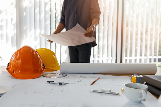 Architect working in a office. engineer holding blueprint in office, architectural concept
