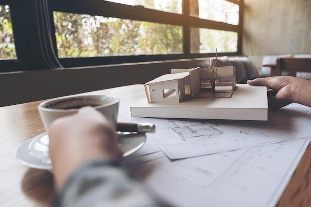 커피를 마시는 동안 가게 그리기 종이와 건축 모델에서 작업하는 건축가