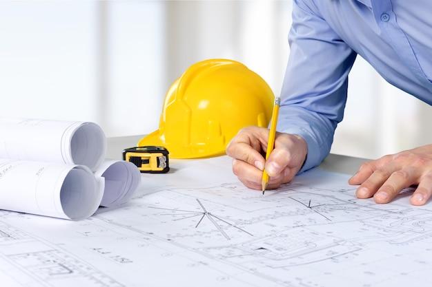Архитектор работает над планом строительства. рабочее место архитектора - архитектурный проект,