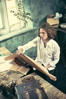 オフィスでの描画テーブルに取り組んでいる建築家