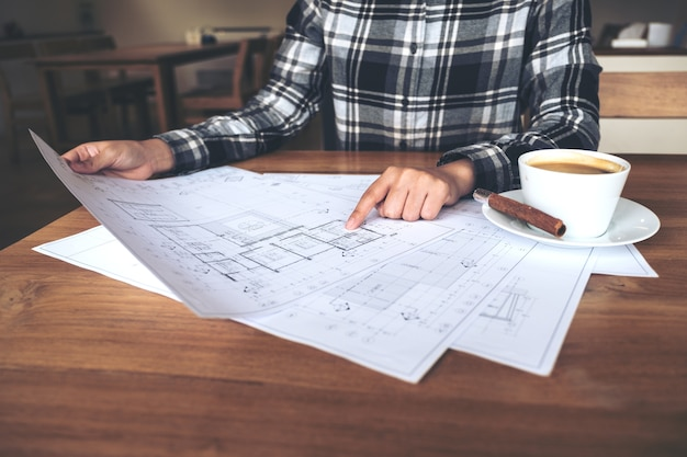 An architect working and pointing at shop drawing paper on table