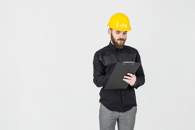 Architect writing on clipboard standing against white background