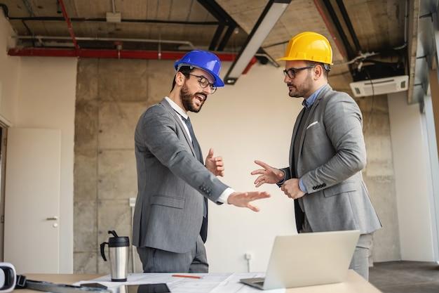 Архитекторы обсуждают свой проект. один архитектор указывает на ноутбук и предлагает нововведения.