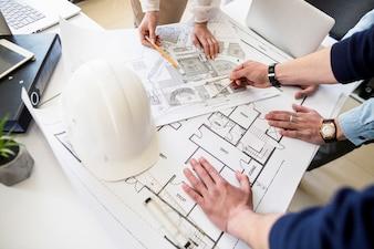 建築家のエンジニアが青写真でテーブルで議論する