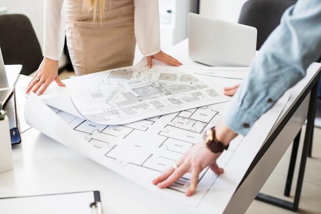 Инженер-архитектор обсуждает за столом с планом