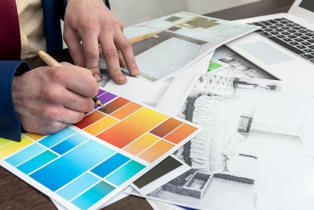 建築家は、クリエイティブなデスク、オフィスで、カラーサンプルとラップトップを使用してモダンなアパートの図面を手渡します。部屋の装飾の色を選ぶ男