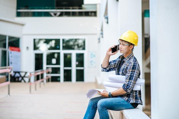 Архитекторы держат планы этажей и разговаривают по телефону.